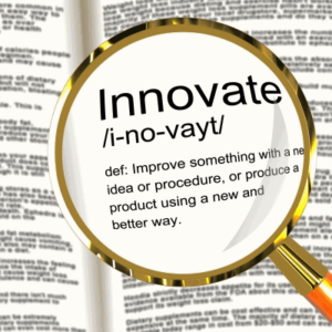 Image of magnifying glass looking up innovate in dictionary