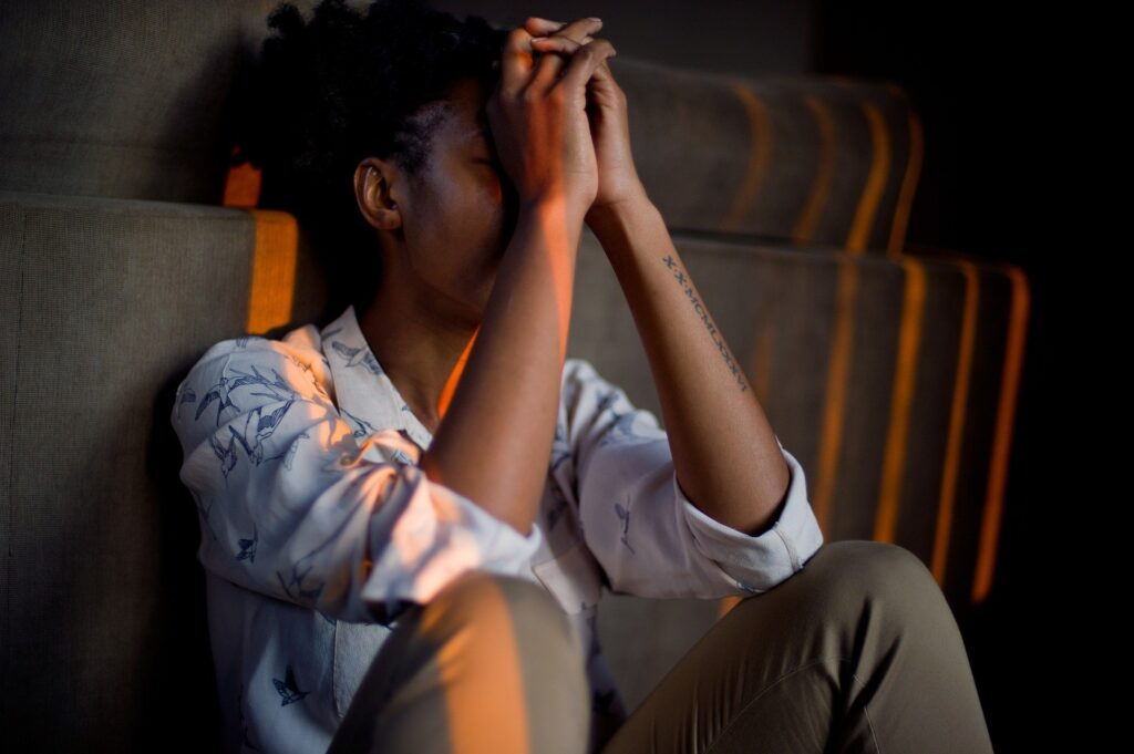 Stressed woman leaning against couch